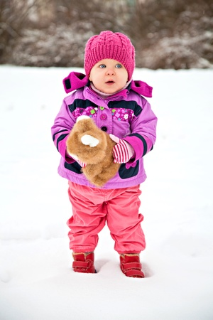 Little pretty girl in winter with the toy rabbit photo