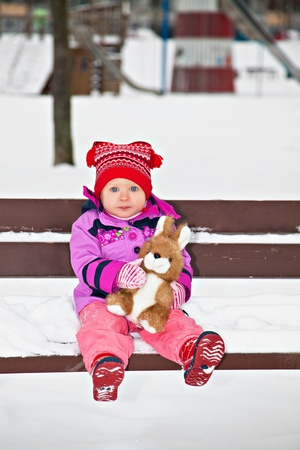 Little girl sitting on the winter bench with her toy rabbit photo