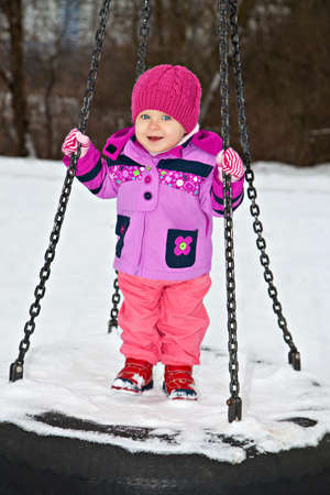 Little smiling girl on winter seesaw photo