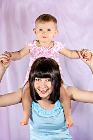 Cute little baby girl on mother shoulders photo