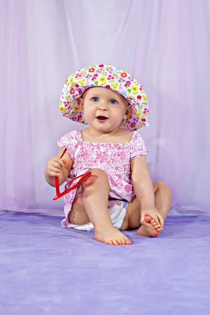 Cute baby girl in a summer hat and sunglasses photo