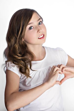 Attractive smiling young girl showing heart gesture with hands photo