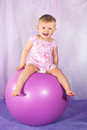 Happy baby girl on the big pink ball Stock Photo