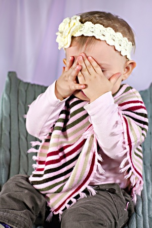 Little girl hiding face, playing hide-and-seek game photo