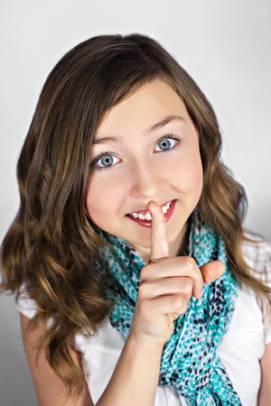 Portrait of young girl gesturing for quiet with finger to lips photo