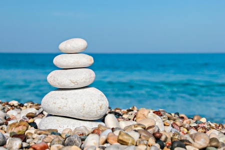 Zen stones stacked at beach against a blue sky and sea with copy space Stock Photo