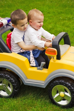 Brother and sister playing in toy car Stock Photo