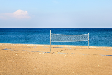 Beach volleyball net with sea in background photo
