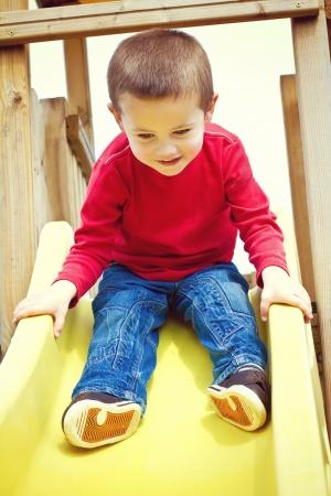 Little boy sliding on children Stock Photo