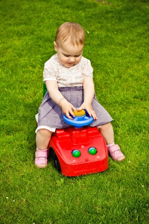 Girl playing in the garden with toy car photo
