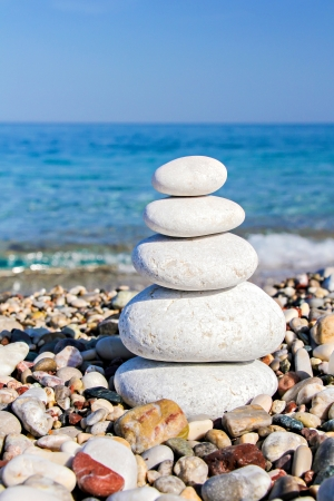 Zen stones stacked at beach against a blue sky and ocean with copy space