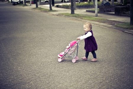 Cute little girl with her toy carriage and doll photo