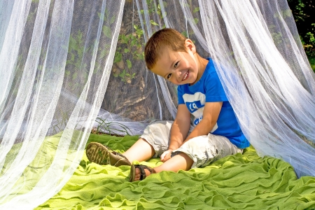 Little boy sitting on the plaid in the marquee Stock Photo