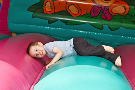 Cute little boy playing on inflatable slide