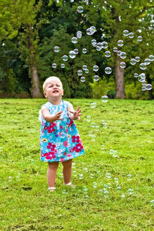 Little girl catching soap bubbles in city park photo