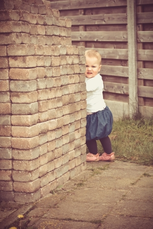 Little girl hiding behind the brick wall photo