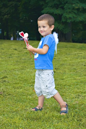 Little boy in the park with small angel white wings and hearts decoration photo