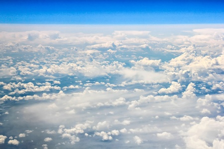 View from an airplane window, flying above white clouds photo