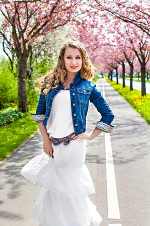 Attractive girl in a park on the cherry blooming tree photo