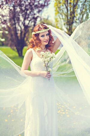 Red-haired beautyful girl with spring blossom photo