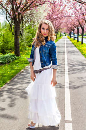 Attractive girl in a park on the cherry blooming trees alley, sunny day, springtime photo