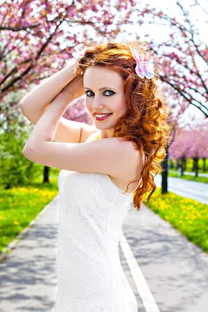 Redhead girl at blooming trees alley, springtime photo