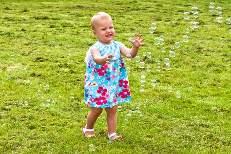 Young girl reaching for soap bubbles photo