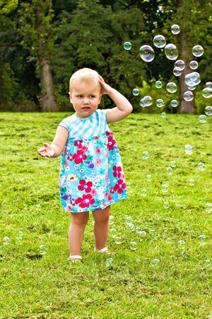 Little girl playing with soap bubbles photo