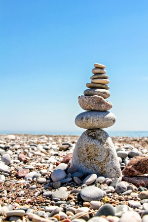 Zen stones stacked at beach against a blue sky and ocean with copy space photo