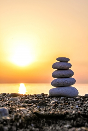 Zen-like stone pyramid on the beach at the sunset Stock Photo