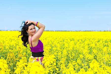 Portrait of a beautiful brunette in violet dress in oilseed rape field photo