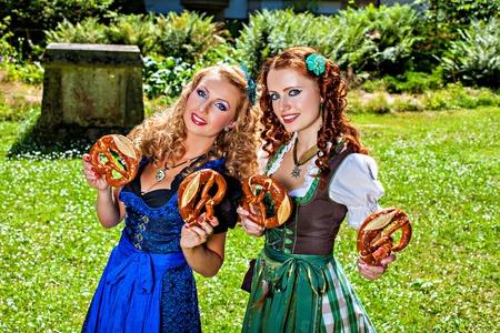 dirndl dress: Two girls in dirndl dress holding pretzel Stock Photo