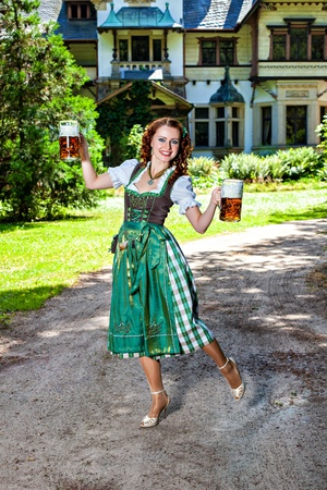 Beautiful bavarian woman holding two big glasses of beer photo