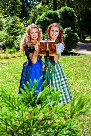 dirndl dress: Two girls in dirndl dress holding Oktoberfest beer stein