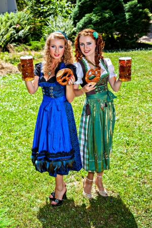 Two girls in dirndl dress holding Oktoberfest beer stein and pretzel photo