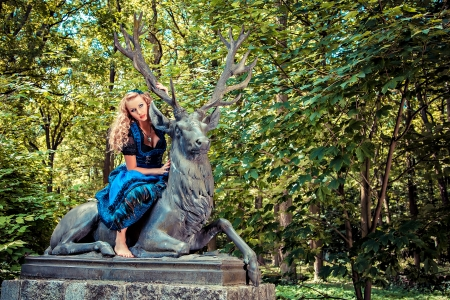 Romantic girl wearing dirndl and sitting on the deer in the forest photo