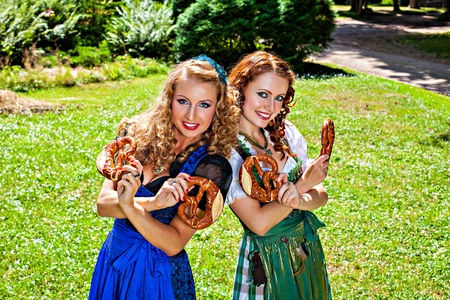 dirndl dress: Two smiling girls in dirndl dress holding pretzel