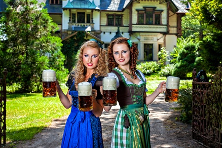 stein: Two girls in dirndl dress holding Oktoberfest beer stein
