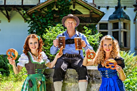 Group of men and women in traditional german Tracht with beer and pretzel photo
