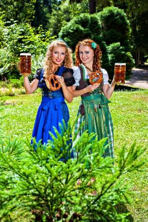 dirndl dress: Two girls in dirndl dress holding Oktoberfest beer stein and pretzel
