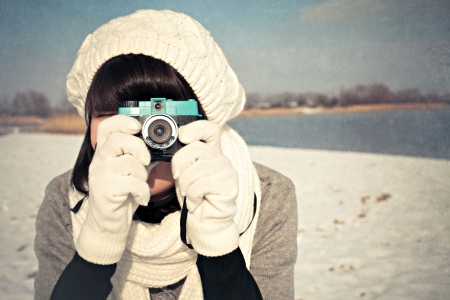 A young female photographer with a camera taking photos