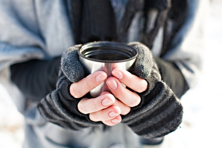 Hands in knitted mittens holding a cup of tea photo