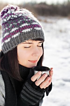 Portrait of the beautiful girl drinking hot tea in snowy winter photo