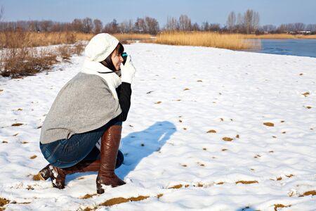 Girl taking a photo at winter lake