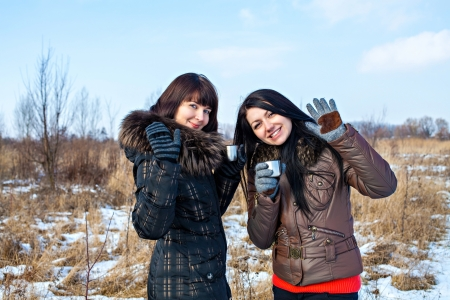 Two beautiful woman friends dressed in winter clothes enjoying a conversation, drinking hot drink and laughing together outdoors photo