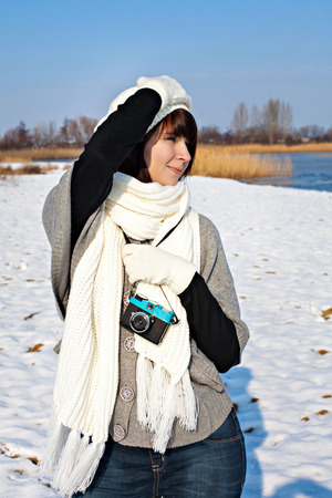 A young female photographer walking with a camera in winter photo