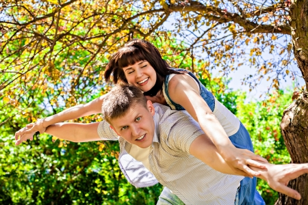 stretched out: Laughing young man giving piggyback to woman, arms stretched out Stock Photo