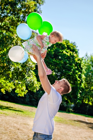 tossing:  Happy young father tossing his daughter outdoors Stock Photo