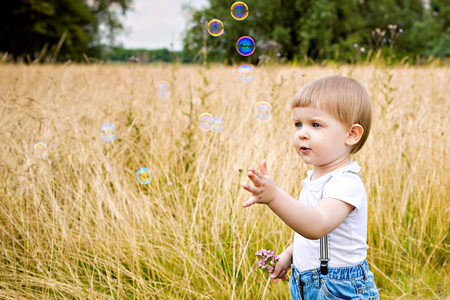 Sweet little girl playing with bubbles on a meadow photo