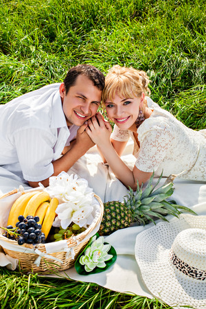 Happy young couple making picnic in the park photo